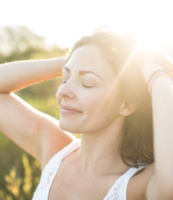 Woman stands in the sun with eyes closed and hands on her head.